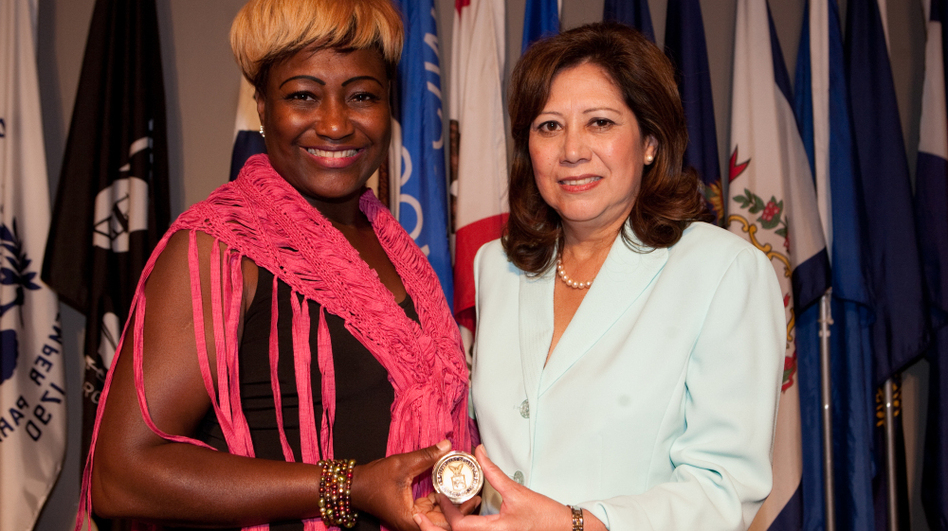 """Lisa Bolling accepts the """"Challenge Coin"""" from Secretary of Labor Hilda L. Solis at Arlington National Cemetery's Women in Military Service for America Memorial on July 20. The secretary shared Bolling's story of being a homeless female veteran at the launch of a new trauma guide for women. (Courtesy Of The Department Of Labor)"""