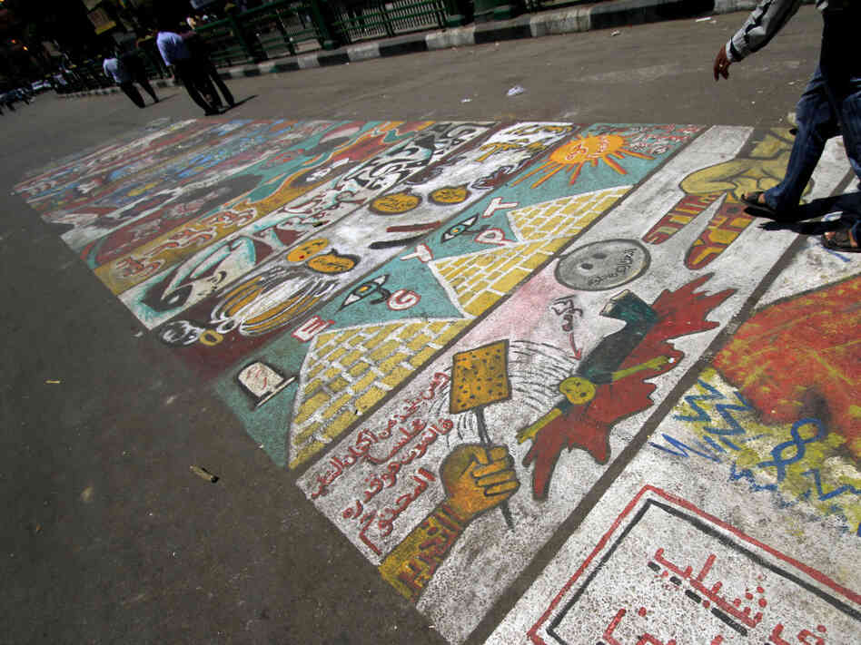 "People walk by graffiti showing an arrow pointing at a man, who represents the government, and a hand beating him over the head with a spatula that reads in Arabic ""Tahrir"" at Tahrir Square in Cairo, Egypt, Saturday, July 23, 2011."