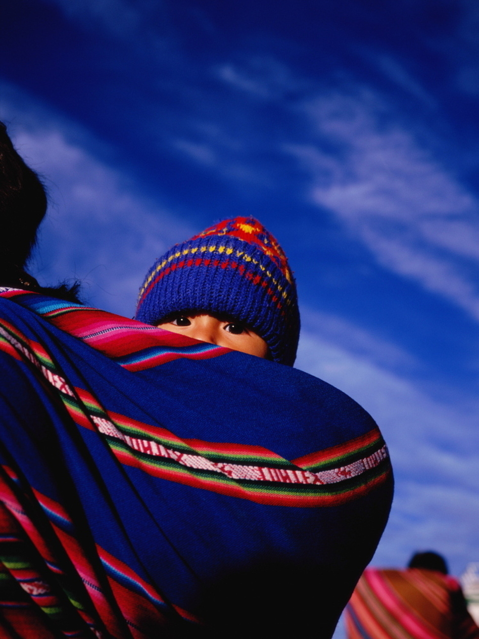A young child wrapped in an <em>aguayo</em>, a traditional sling, on mother's back in La Paz, Bolivia.