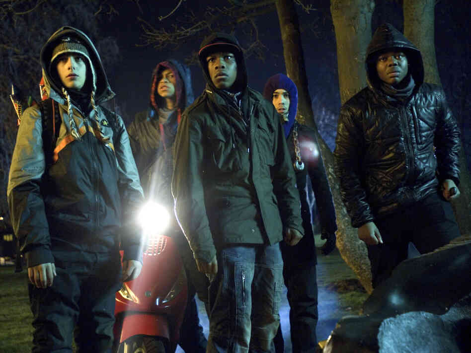 The fate of the world rests on a group of neighborhood toughs in a South London apartment building in Attack The Block. Their leader, Moses (John Boyega, center), robs a defenseless woman in the film's first scene.