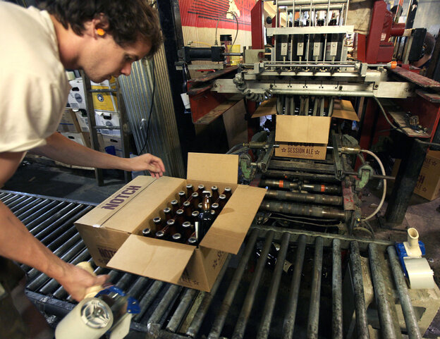 """Cellarman Cooper Reid packs cases of beer at the Ipswich Ale Brewery in July. New rules put out by the state's alcohol commission require """"farmer-brewers&qu"""