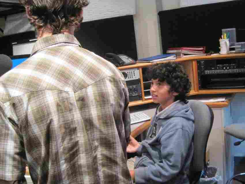 KAZU's Production Assistant Andrew Kramer shows Caetano around the control room.