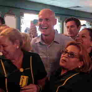 Florida Governor Rick Scott (C)  surrounded by workers at a Miami restaurant, July 12, 2011.