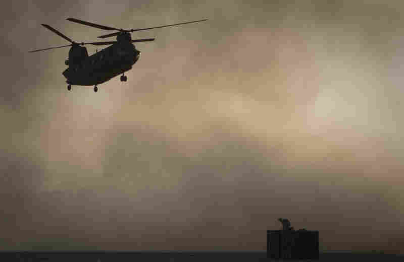 A U.S. Marine tries to take cover as a Chinook helicopter arrives at Forward Operating Base Edi in the Helmand Province of southern Afghanistan, Thirty Americans were killed when a helicopter crashed in eastern Wardak province early Saturday.