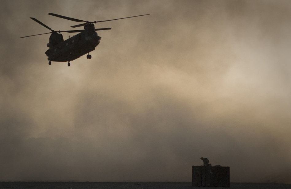 A U.S. Marine tries to take cover as a Chinook helicopter arrives at Forward Operating Base Edi in the Helmand Province of southern Afghanistan, Thirty Americans were killed when a helicopter crashed in eastern Wardak province early Saturday. (Anja Niedringhaus/AP)