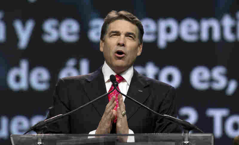 Texas Gov. Rick Perry prays at a daylong rally in Houston on Saturday. Perry attended the prayer rally despite criticism that the event inappropriately mixes religion and politics.