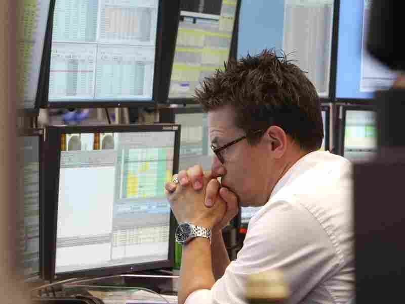 A broker watches screens displaying the German stock index DAX at the stock market in Frankfurt, Germany, on Monday, where the stock index fell after the opening of trading.
