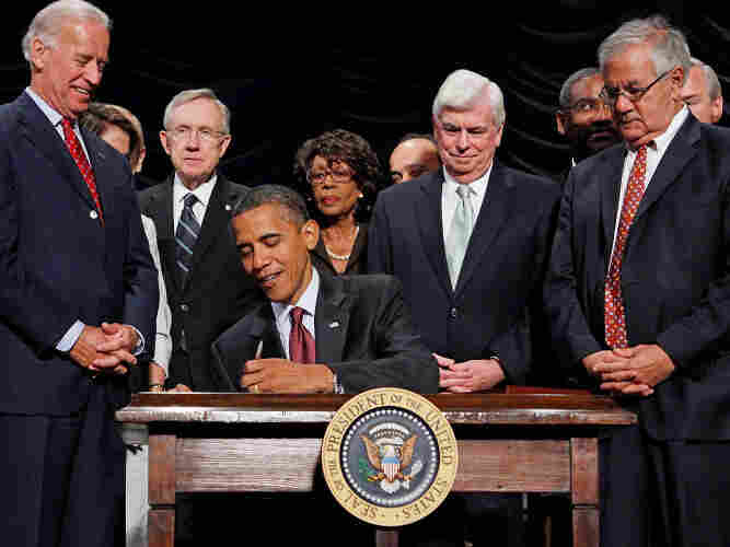 President Obama signs the financial reform bill into law in 2010 as Vice President Biden and lawmakers look on.