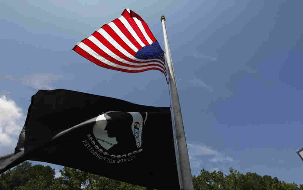 A U.S. flag and a POW/MIA flag fly at half-staff at a sports bar near the main gate of Naval Air Station Oceana/Dam Neck Annex, the base of Navy SEAL Team Six in Virginia Beach, Va., Monday.