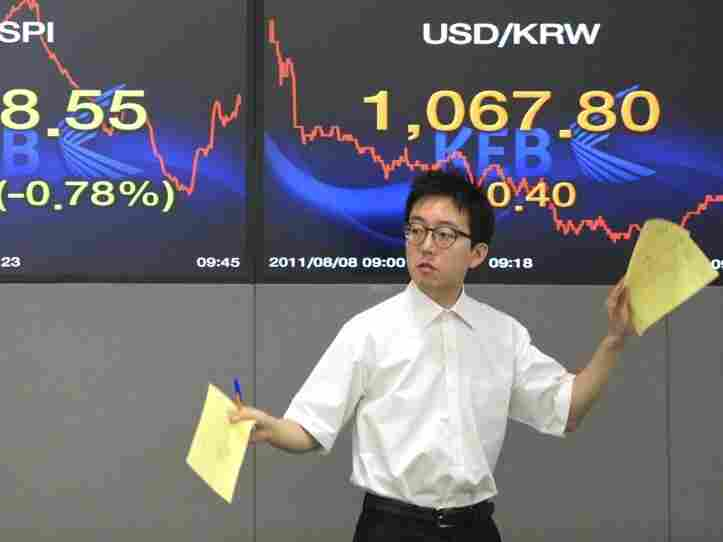 A currency trader gestures Monday in front of screens showing the Korea Composite Stock Price Index, left, and the exchange rate between the U.S. dollar and the South Korean won at the Korea Exchange Bank headquarters in Seoul, South Korea.
