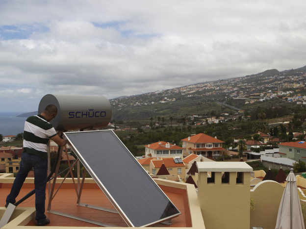 A worker installs a solar panel on the roof of a house in Santa Cruz de Tenerife in the Spanish Canary Island of Tenerife in March 2011. The country's solar sector intends to double its contribution to the national grid by 2020, after an earlier government attempt at boosting the industry failed.