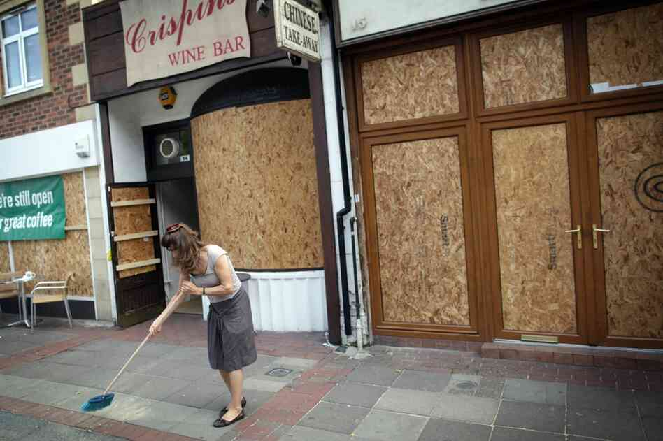 A shop owner sweeps up outside her property in Ealing, London on Aug. 10. After three nights of rioting and looting in and around London, the chaos has spread to other cities around Britain.