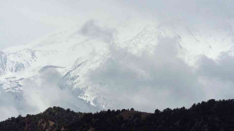 FILE - In this May 13, 2004 file photo, clouds swirl around Mount Sopris as the peak hangs over a subdivision south of Glenwood Springs, Colo. A movement to name a Colorado mountain peak after the late John Denver has hit a snag.