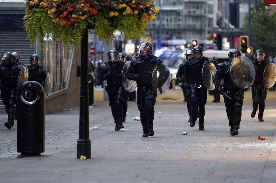 Riot police patrol the street in Manchester on Aug 9. Britain began flooding London's streets with 16,000 police officers, nearly tripling their presence, to combat the worst rioting in a generation.