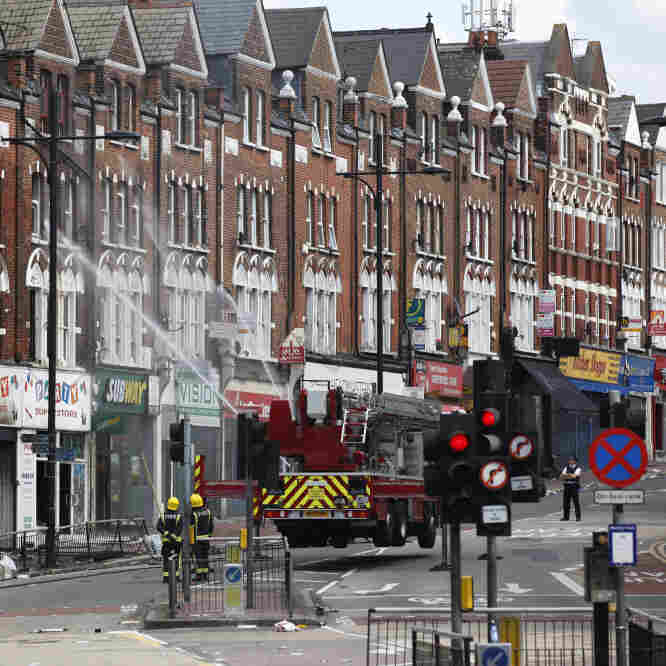 Firemen hosed down an area of Clapham, South London, on Tuesday after another night of violence left trails of looted stores, wrecked cars and burned buildings across London and several other cities.