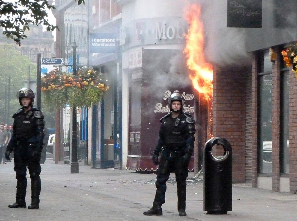 Fire rips through a retail store in Manchester, in northwest England, Tuesday, marking a fourth night of violence in Britain. Looters have targeted electronics and clothing stores.