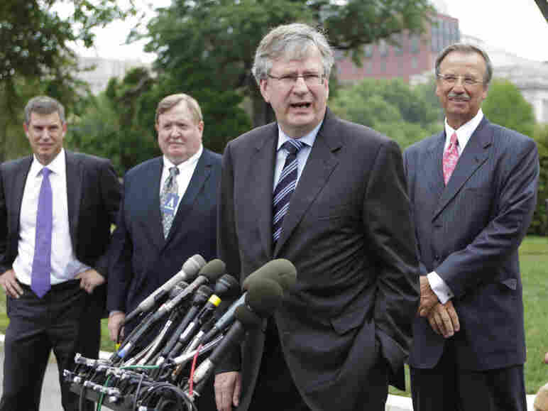 Daimler Trucks North America President and CEO Martin Daum, center, speaks with reporters outside the White House Tuesday after he and other executives met with President Obama to discuss new fuel efficiency standards.