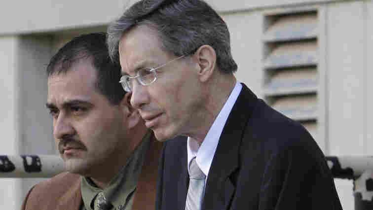 Warren Jeffs, right, is escorted out of the Tom Green County Courthouse by a law enforcement officer.