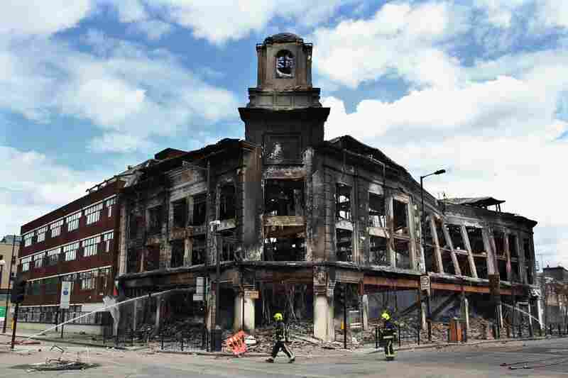 Fireman walk past the smoldering remains of a burned-out building after riots on Tottenham High Road in North London, Aug. 7.