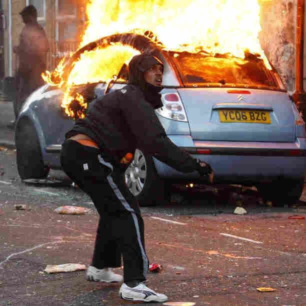 "A rioter throws a rock at riot police in Clarence Road in Hackney, London, Monday. The wave of violence has spread to three other major British cities. The riots appeared to have little unifying cause â€"" though some involved  claimed to oppose sharp government spending cuts, which will slash  welfare payments and cut tens of thousands of public sector jobs through  2015."