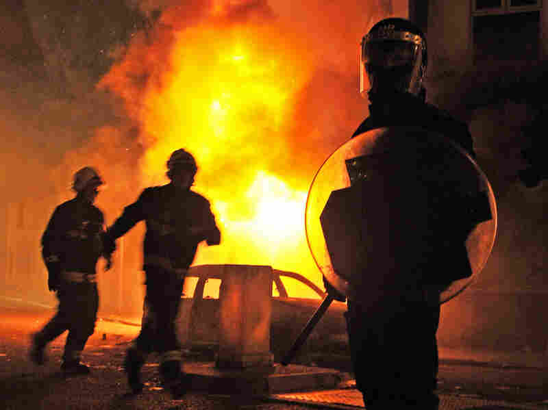 A British riot policeman stands guard in front of a burning building and burnt out car in Croydon, South London on August 8, 2011.