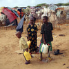 Children from southern Somalia fill jugs with water at a refugee camp in Mogadishu Tuesday. The number of people fleeing famine-hit areas of Somalia is likely to rise dramatically and could overwhelm international aid efforts in the Horn of Africa, a U.N. aid official said Tuesday.