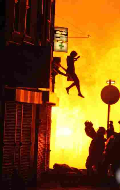 A woman can be seen jumping from a burning building in Croydon on Aug. 8.