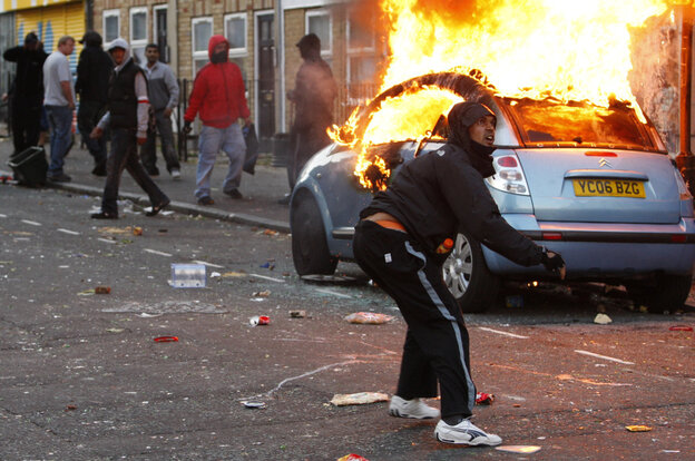 A rioter throws a rock at police in Clarence Road in Hackney on Tuesday in London.
