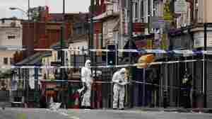 Police forensic officers work at the scene where three people were killed after being struck by a vehicle Wednesday in the Winson Green area of Birmingham, England.