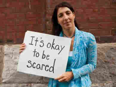 "One of women in the video holds up a sign that says, ""It's okay to be scared."""