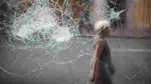 A woman walks past a broken cafe window in London earlier today (Aug. 10, 2011).