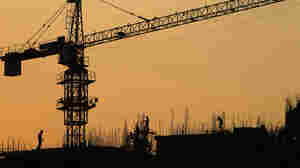 Workers construct an apartment building in Greater Noida, on the outskirts of New Delhi, India, Aug. 3, 2011. As many as 100,000 new apartment units are scheduled to be built on land that previously belonged to farmers. A court has halted some development on the grounds that the farmers weren't fairly compensated.