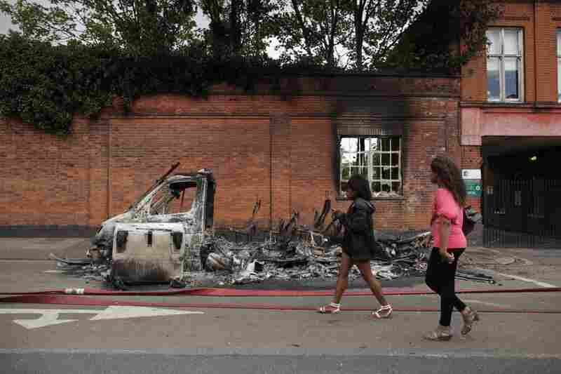 The rioting began in Tottenham after the police shooting that killed Duggan on Aug. 4. Women pass by a burned-out van on Tottenham High Road on Aug. 7.