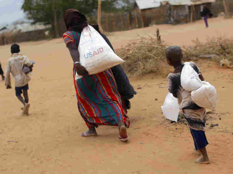A Somali family carries their supply of food aid as they arrive at a refugee camp outside  Dadaab in northeastern Kenya along the Somali border, Aug. 5, 2011.