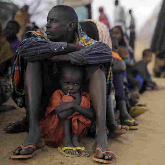 A Somali father sits with his daughter at the head of the line at a refugee camp registration center in Dabaab in northeastern Kenya, Aug. 2, 2011. International aid agencies are struggling to bring in more supplies to drought-stricken Somalia and neighboring Kenya.