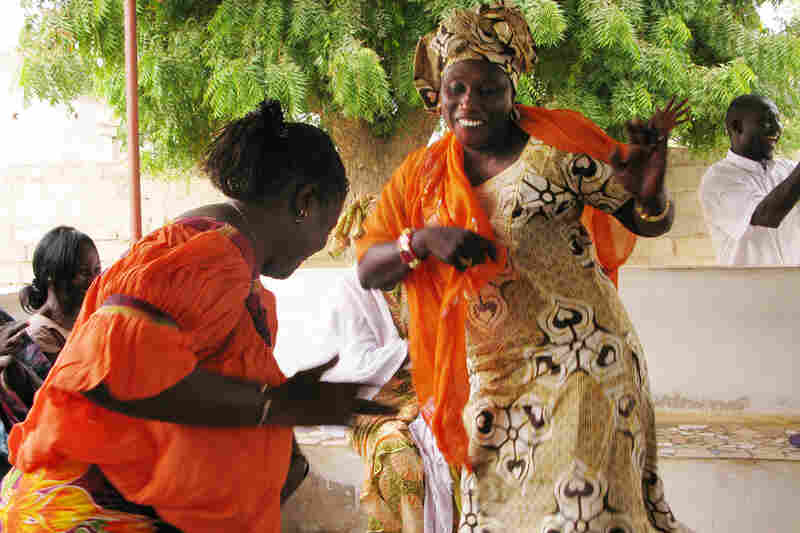 Grandmothers or senior women, called  les grandes-meres, dance during a gathering for women in Guereo, Senegal. In a tradition of solidarity called  bajenu gox, the older women assist younger women in the community.