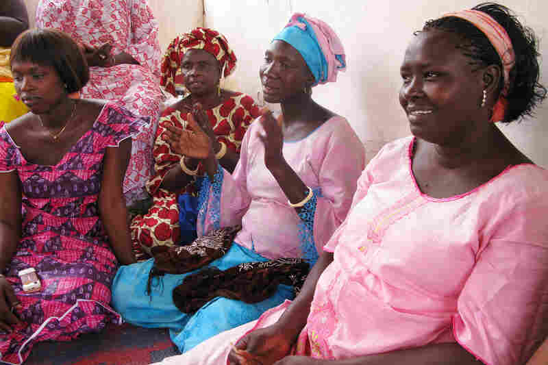 Pregnant younger women, dressed in pink, share with the older women things they have learned about prenatal care from aid groups like ChildFund.