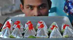 A vendor sells betel leaf wrapped in silver foil in Lucknow, India.