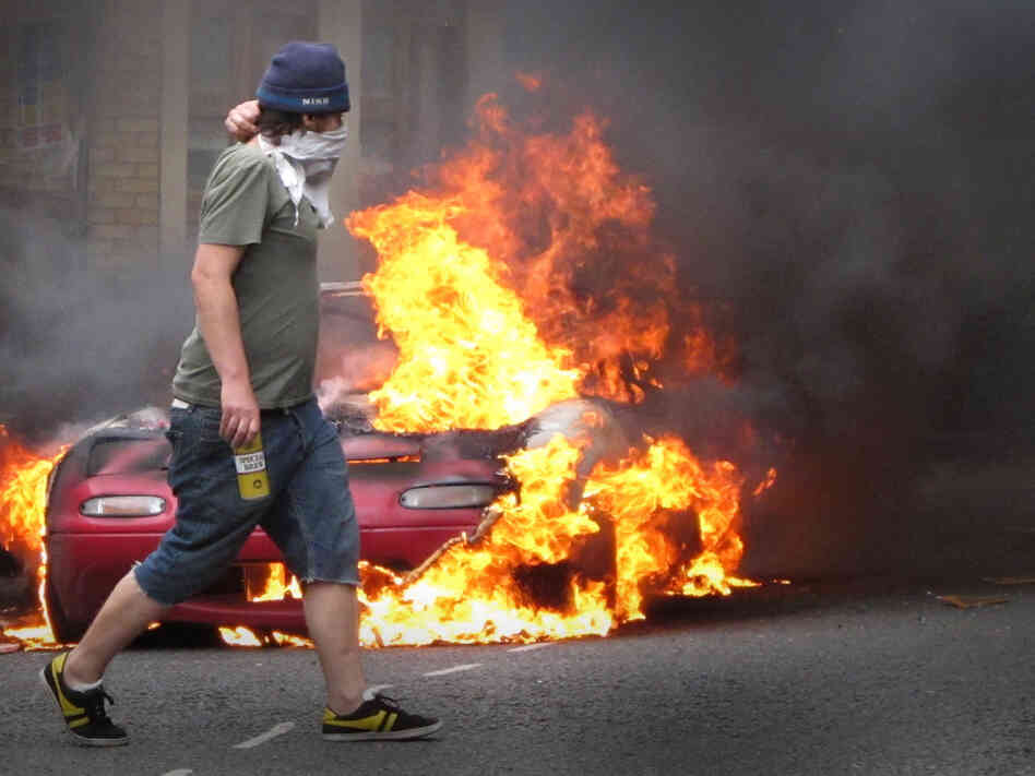 This masked man walked past a burning car in London on Monday (Aug. 8, 2011).