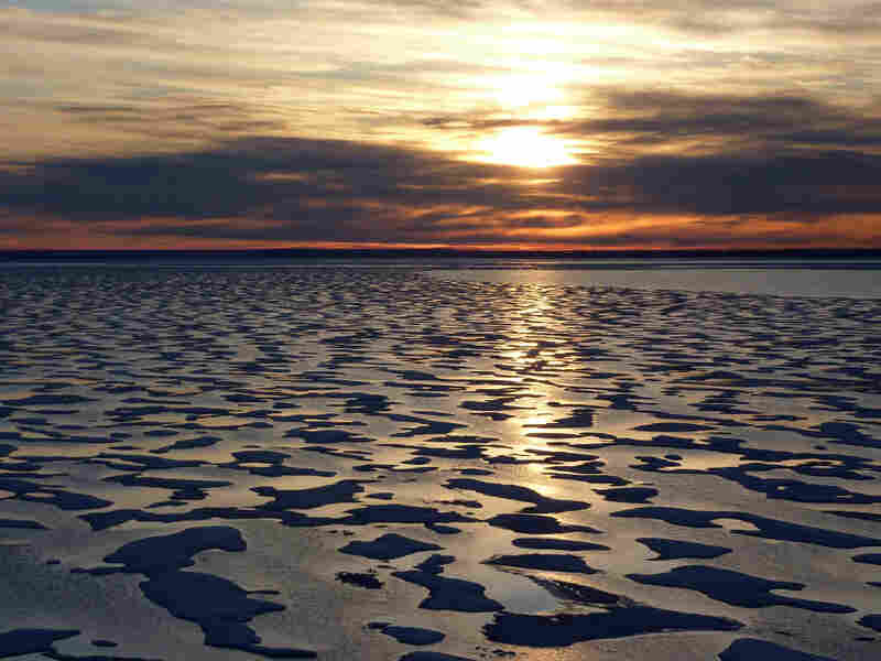 Much  of the Northwest Passage experiences 24 hours  of light during the summer months. But as the Louis heads further  south toward Cambridge Bay, a sunset appears on the  horizon.