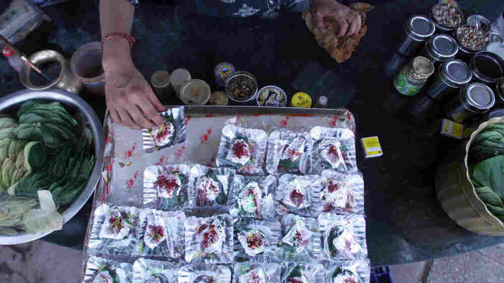 In India, the centuries-old tradition of chewing betel leaves, or paan, spread with spices and sweeteners is losing popularity. In this file photo from 2006, an Indian shopkeeper arranges silver foils of paan at his roadside shop in New Delhi.