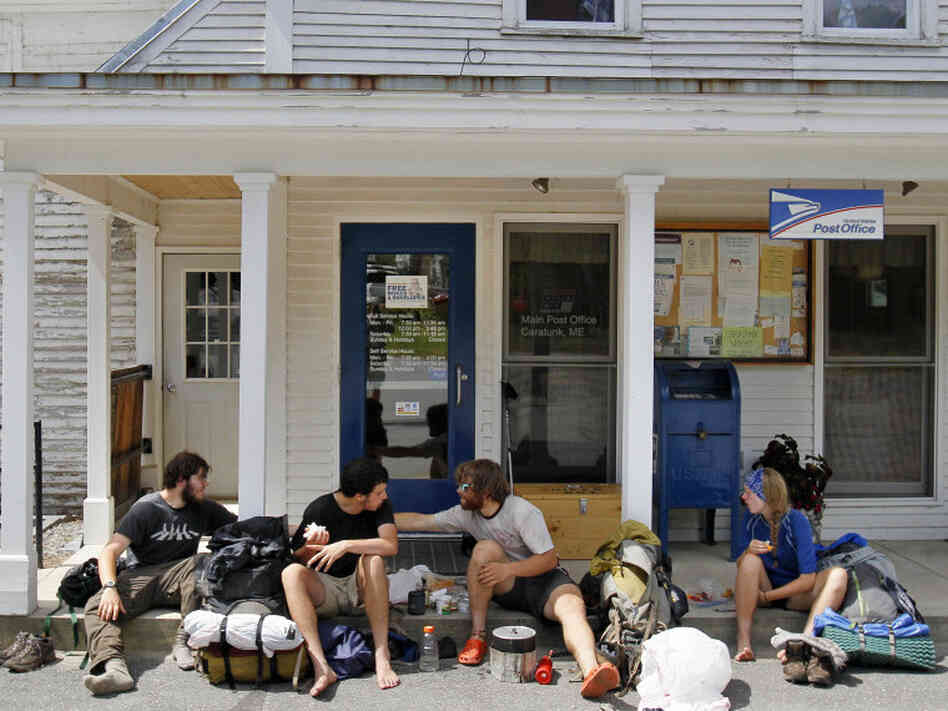 In many rural areas, post offices aren't just about mail. They are community centers. Appalachian Trail thru-hikers prepare lunch outside the post office in Caratunk, Maine. Many hikers rely on this office for vital supply drops.