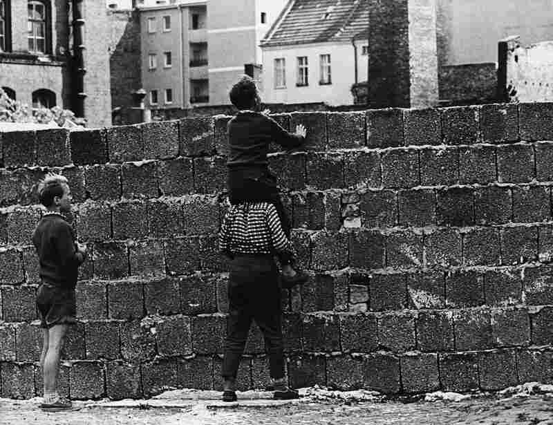 A boy sitting on the shoulders of another child peers over the wall at Liesen Street in West Berlin on Aug. 23, 1961.