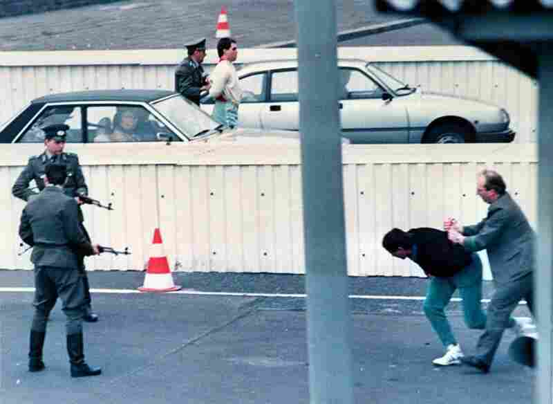 Two East Berlin refugees are taken away by border guards after a thwarted attempt to cross into the West at the Chausseestreet border crossing on April 10, 1989.
