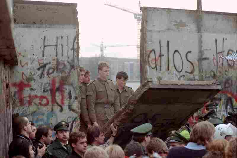 East German border guards stand at a gap in the Berlin Wall after demonstrators pulled down a segment of it on Nov. 11, 1989.