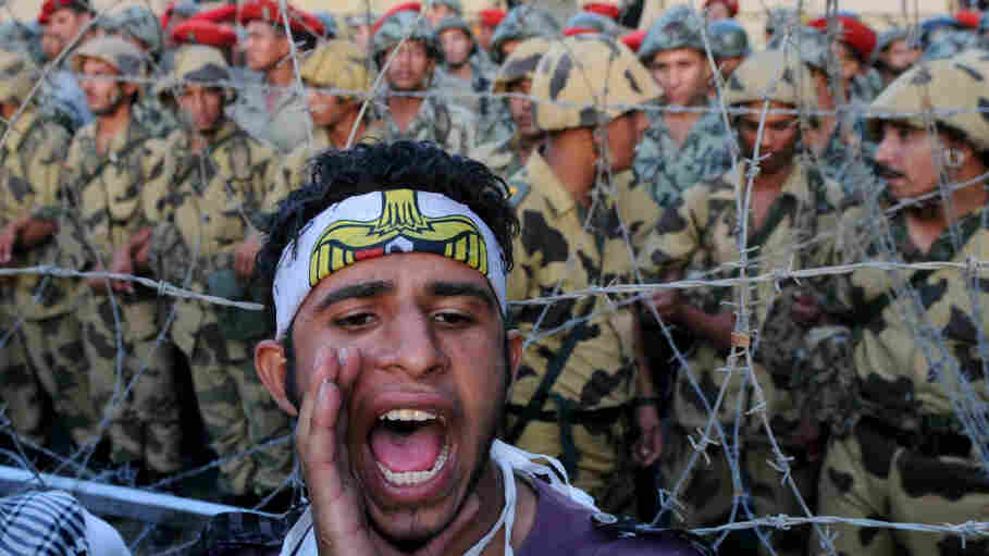 A protester shouts as Egyptian soldiers stand guard behind barbed wire at the Defense Ministry in Cairo on July 23. Egyptians say their revolution is still not complete, but they believe they are setting the tone for the region.