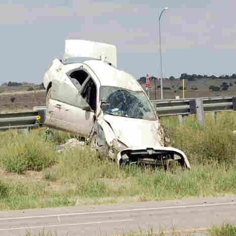 The Subaru Impreza driven by three fugitive siblings, seen here crashed on a highway barrier Wednesday, was loaned to Ryan Dougherty, the AP says. The photo was provided by the Huerfano Journal.