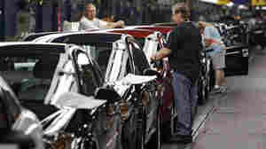 In a file photo, workers at General Motors' Lordstown Assembly plant in Lordstown, Ohio put the final touches on 2011 Chevrolet Cobalts. The weakening dollar will allow U.S. automakers to export at a financial advantage.