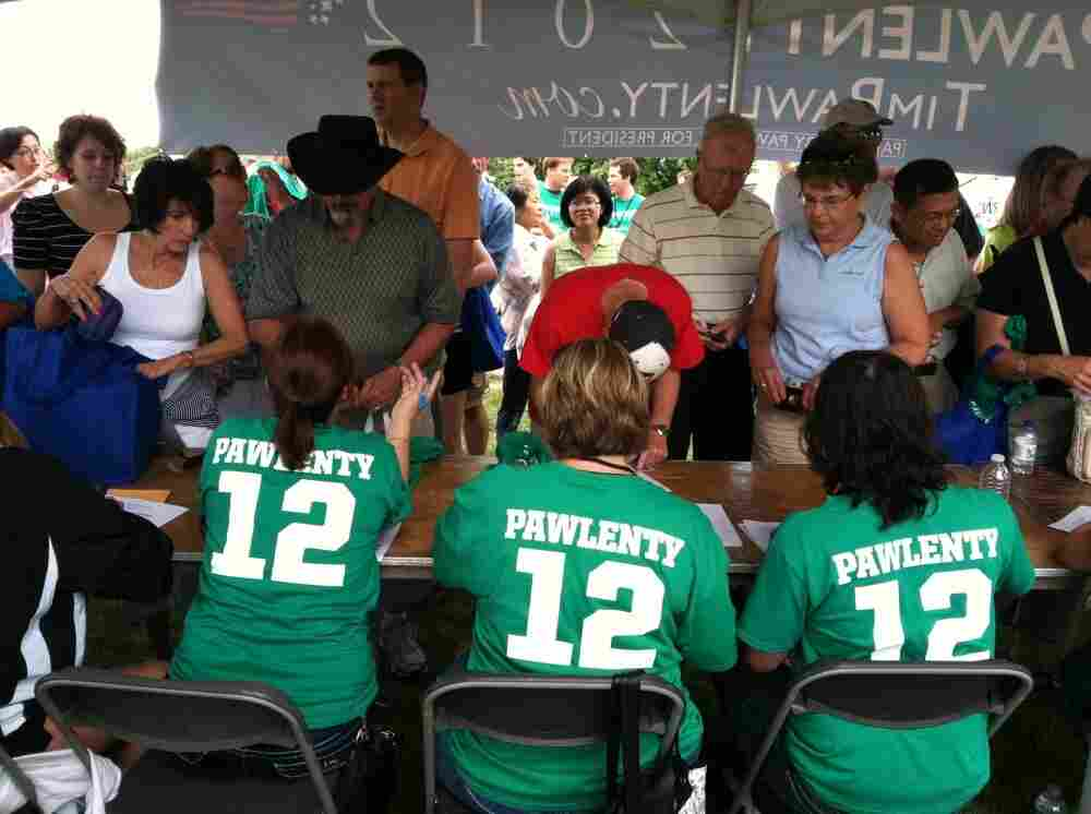 """Volunteers for former Minnesota Gov. Tim Pawlenty take information from participants and hand out  """"Pawlenty 2012"""" T-Shirts at a table near a food tent the campaign set up for supporters."""