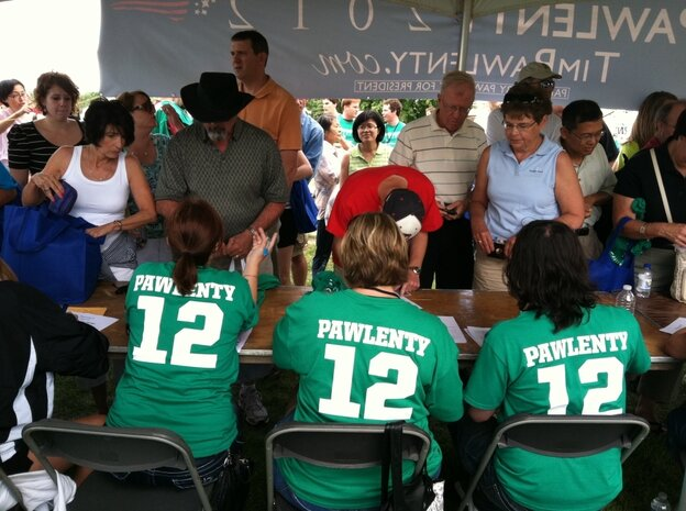 """Volunteers for former Minnesota Gov. Tim Pawlenty take information from participants and hand out  """"Pawlenty 2012"""" T-Shirts at a table ne"""